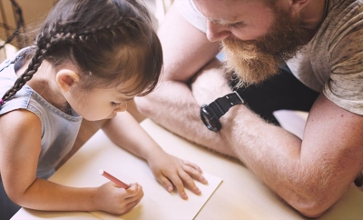 Father watches lovingly as his younger daughter writes or draws.
